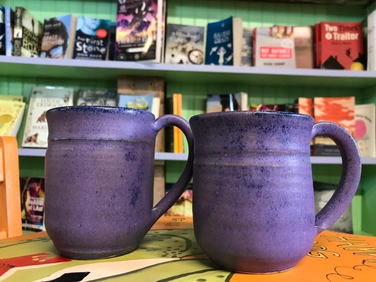 Purple pottery mugs at Mabel Murple's Book Shoppe & Dreamery